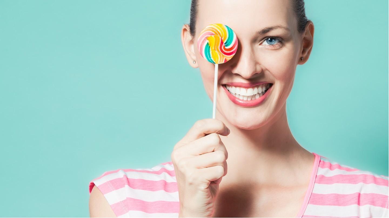 Frau mit schön gepflegten Zähnen hat einen Lolli in der Hand.
